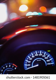 blue light from speedometer on car dashboard with blur steering wheel , and bokeh lights from city street behind
