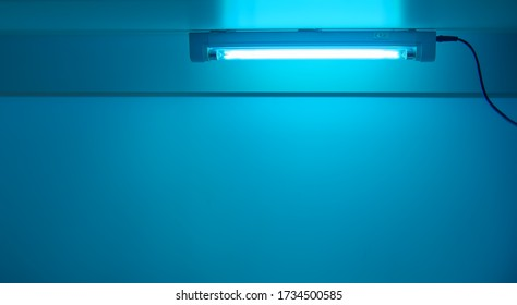 Blue light from ultraviolet lamp. UV lamp sterilization of air and surfaces. Coronavirus epidemic prevention concept. Copy space
