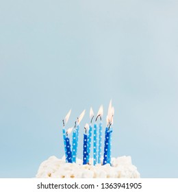 blue lighted candles birthday cake against blue backdrop