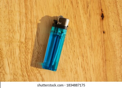 Blue lighter on a light colored wooden table