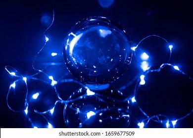 blaue Lichter umgeben eine glasklare Kugel auf einem Spiegel