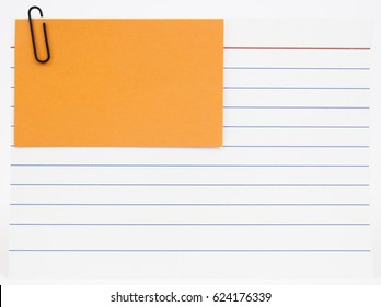 Blue lined index card with orange notecard attached with red paperclip. Isolated.