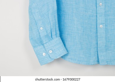 Blue linen shirt cuff on a white background