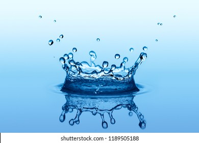 Blue liquid splash in shape of crown with small water drops