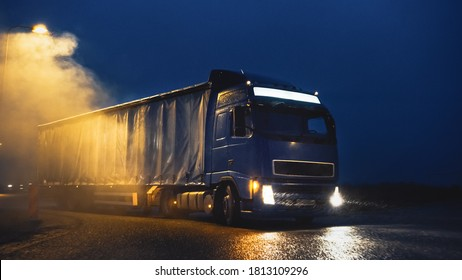 Blue Long Haul Semi-Truck with Cargo Trailer Full of Goods Travels At Night , Turning on Freeway Road, Driving Across Continent Through Rain, Fog Snow. Industrial Warehouses Area.