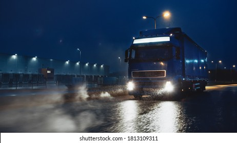 Blue Long Haul Semi-Truck with Cargo Trailer Full of Goods Travels At Night on the Freeway Road, Driving Across Continent Through Rain, Fog, Snow. Industrial Warehouses Area.