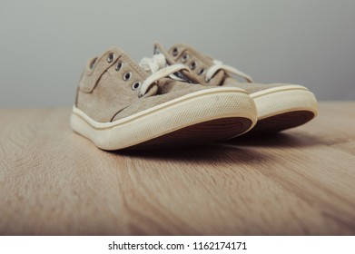 Blue lovely used sneakers on wooden desk