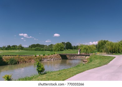 A blue loving couple sits on a bridge near a small river. Blue-green landscape. Smooth lawn ..