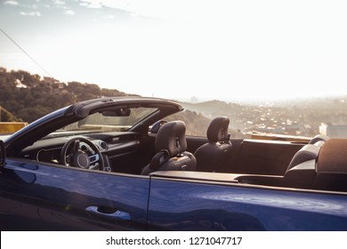 Blue luxury car in gazebo overlooking the city of Barcelona at sunrise