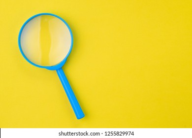 Blue magnifying glass, magnifier on yellow background with copy space using as search, transparent, science discovery or SEO concept.