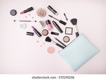 A blue makeup bag with cosmetic beauty products spilling out on to a pastel pink background