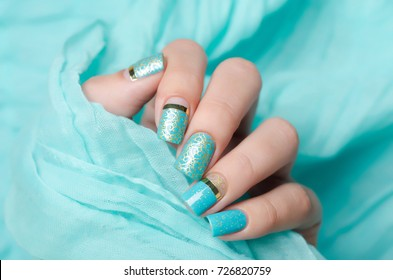 blue manicure with gold glitter and gold ornament and golden strip