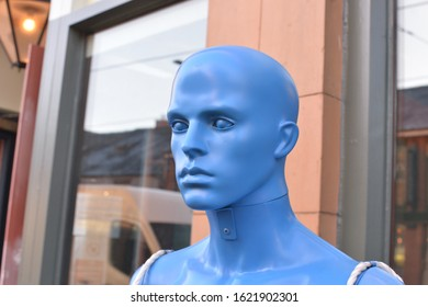 A blue mannequin model head for hanging clothes on outside a fashion shop