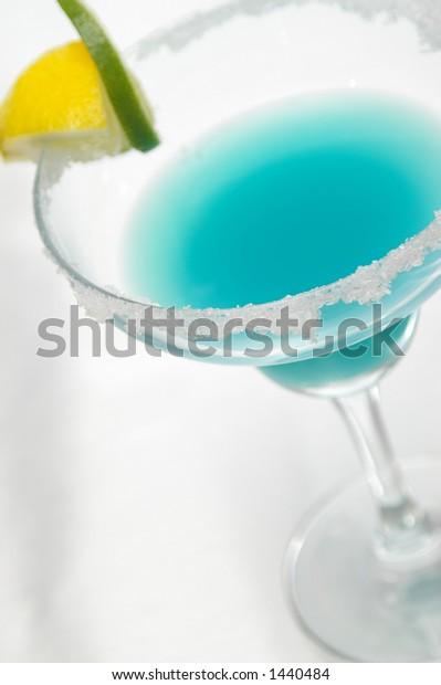 Blue margarita garnished with sugar, lemon and lime.