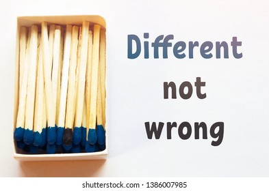 Blue matches and one match of black color in a box. Difference, self respect and acceptance concept. Motivational phrase on the image. Opposition, not like others concept.