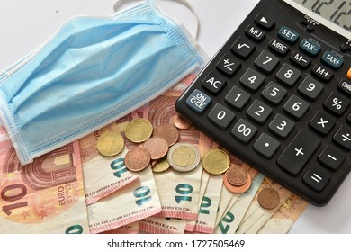 Blue medical facemask on top of euro bills symbolising the concept of economic fallout due to coronavirus.