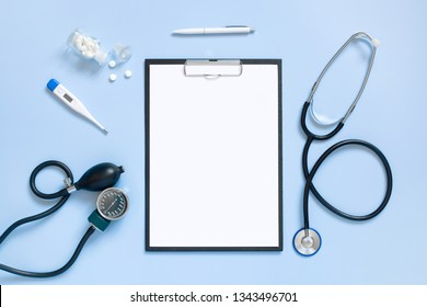 Blue medical mock-up with blank sheet of paper on the clipboard and stethoscope, copy space