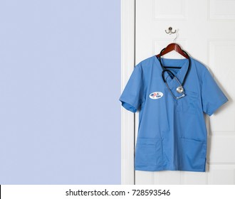 Blue medical scrubs uniform shirt hanging on a hook with I Vote sticker to illustrate healthcare issue in USA