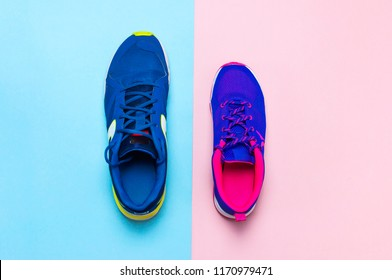Blue mens and violet-pink female sneakers on pastel pink and blue background flat lay top view with copy space. Sports shoes, fitness, concept of healthy lifestile, everyday training.