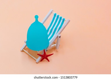 Blue Menstrual cup with a blue deck chair on a peach pastel background. The concept of simplicity and comfort of using the menstrual cup in travel.
