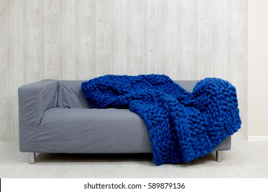 Blue merino wool blanket on grey sofa. Blanket of thick yarn. Chunky knit.