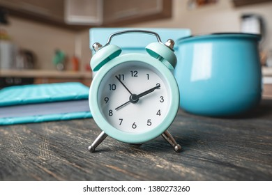 Blue metal alarm clock on the table with a mug and a diary on the background of the kitchen. Concept of time and home mode