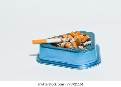 Blue metal ash tray overflowing with cigarette buds and ash isolated on white background