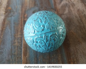 blue metal ball on brown wooden table