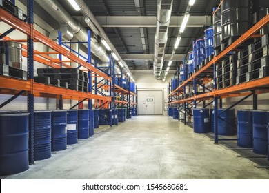 Blue metal barrels. Chemical industry. Metal barrels for chemicals. Storage racks. Barrels are stored in a warehouse. Warehouse storage.
