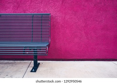 Blue metal bench on concrete floor with purple stucco textured wall in background.