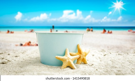 A blue metal bucket with free space for your product. The possibility of mounting bottles with drink, ice cream, food or other products. Blurry beach with people and ocean view. Summer time and sunny