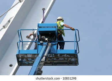 Blue metal cherry picker with workers partially in view,working on a small section of a bridge girder, set against a blue sky.