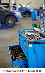 Blue metal tool cabinet with open case at service station, shallow dof
