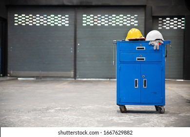 Blue metal tool cabinet with safety helmets, glove, document pad on the cabinet with garage background. Automobile repair service.