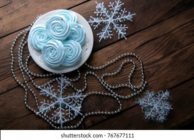 Blue mini meringues and christmas decorations on a wooden background