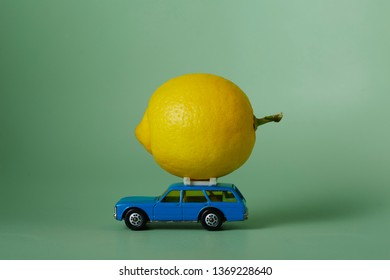 blue miniature toy station waggon with real size lemon on roof rack and green backround.