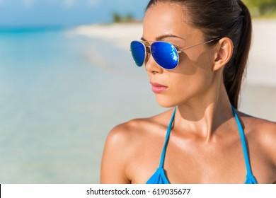 Blue mirror aviator sunglasses sexy woman beauty. Beach bikini Asian model wearing fashion eyewear trendy mirrored glasses and turquoise swimwear looking at the ocean.