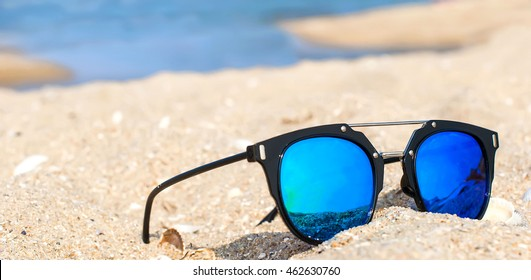 9aacddc1f3 blue mirrored sunglasses on the sand overlooking the sea