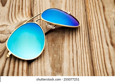 blue mirrored sunglasses on the wooden background close up. horizontal