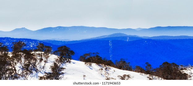 BLue mist over mountains ranges in Kosciuszko national park of Australia in winter season when high country slopes are covered by snow in Perisher valley ski resort.