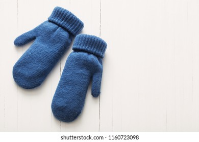 blue mittens on white wooden background
