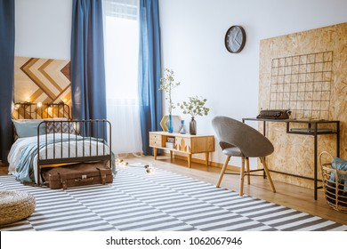 Blue, modern bedroom interior for a boy with gray armchair at a wooden desk and bed with metal frame