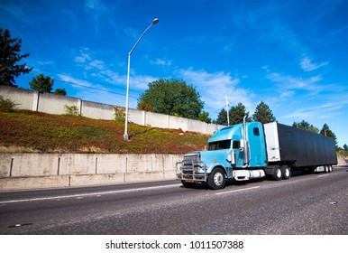 Blue modern big rig long distance semi truck with protective grille guard and black covered trailer for commercial cargo transportation running on straight wide highway in good weather day with sky