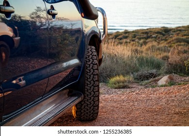 A blue modern SUV with off-road tyres parked near the ocean in Western Australia. It is on an adventurous journey. Road trips are a popular lifestyle type of vacation
