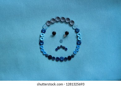 Blue monday concept. Sad smile and tear on face icon made with buttons on blue background.