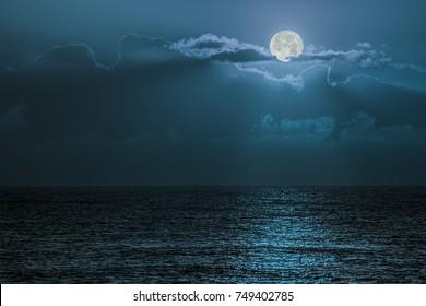 Blue moon light reflecting off ocean. Romantic twilight moonlight glistening off the surface of sea water. Lunar influence.