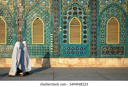 The Blue Mosque in Mazar-i-Sharif, Balkh Province in Afghanistan. Two women wearing white burqas (burkas) walk past a wall of the mosque adorned with colorful tiles and mosaics. Northern Afghanistan.