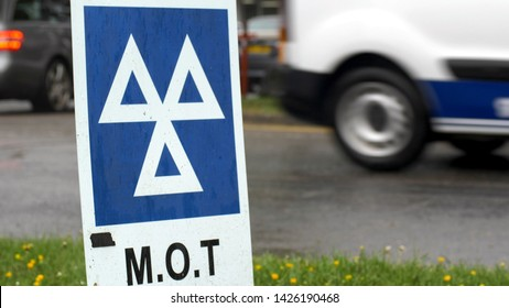 Blue MOT service sign on british road on cloudy rainy day.