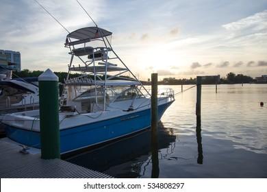 blue motor boat docked in the sunset
