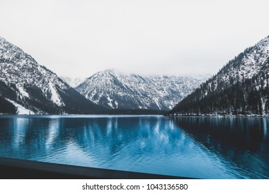 A blue mountain lake with snow capped mountains in the background. The colors in this one are magnificent.